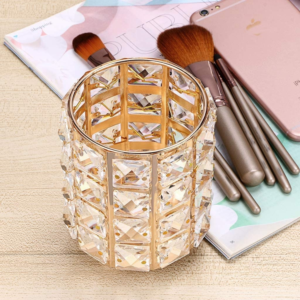 A sparkly cylindrical container on a desk beside makeup brushes