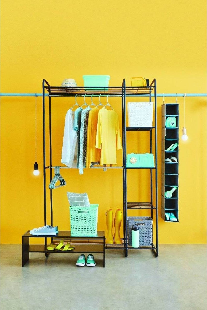 The closet organizer made of black metal tubing, with a top shelf, bottom shelf, three shelves on the right side, and hanging racks running from the top and middle of the organizer