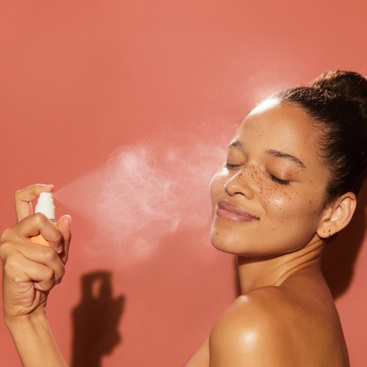 model spraying the mist on her face