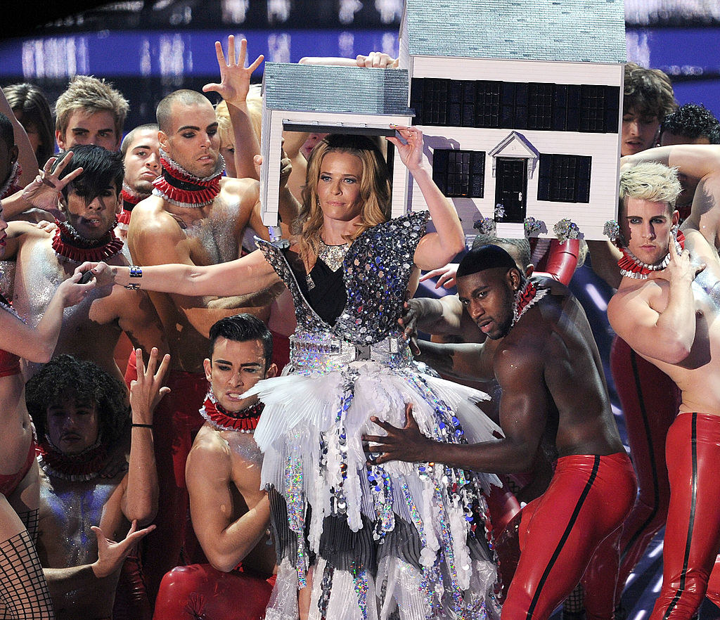 Chelsea Handler on stage wearing a doll house on her head and surrounded by shirtless back-up dancers