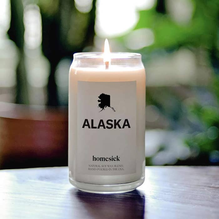 A lit Alaska-scented homesick candle on a tabletop.