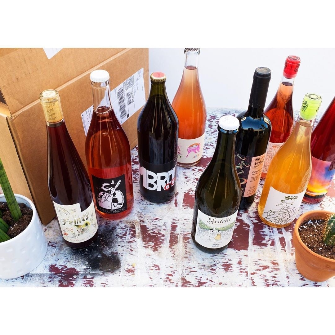 A handful of colorful wine bottles including reds, whites, rosés, and orange wines with colorful labels.