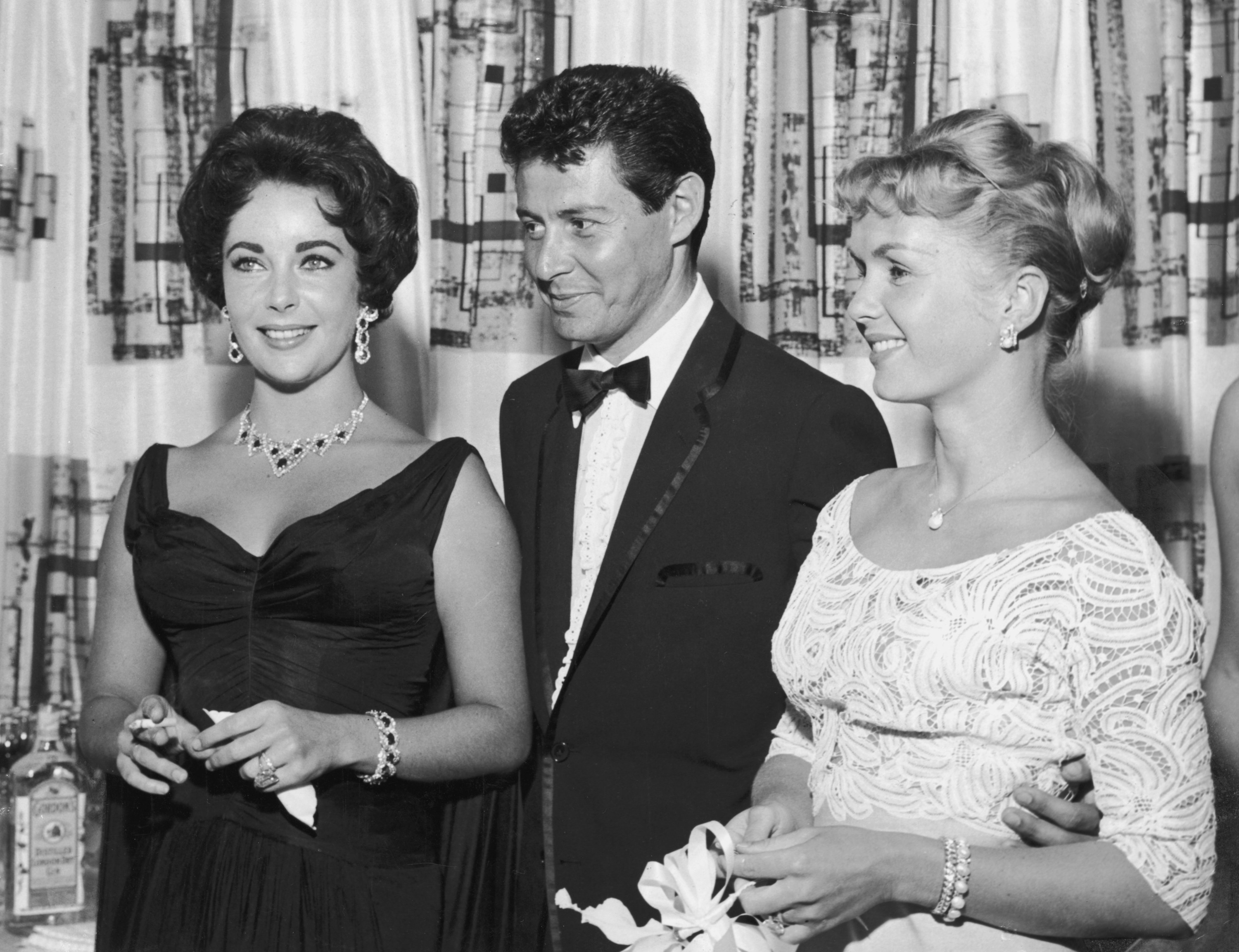 A photo of Elizabeth Taylor, Eddie Fisher, and Debbie Reynolds at a party in 1958