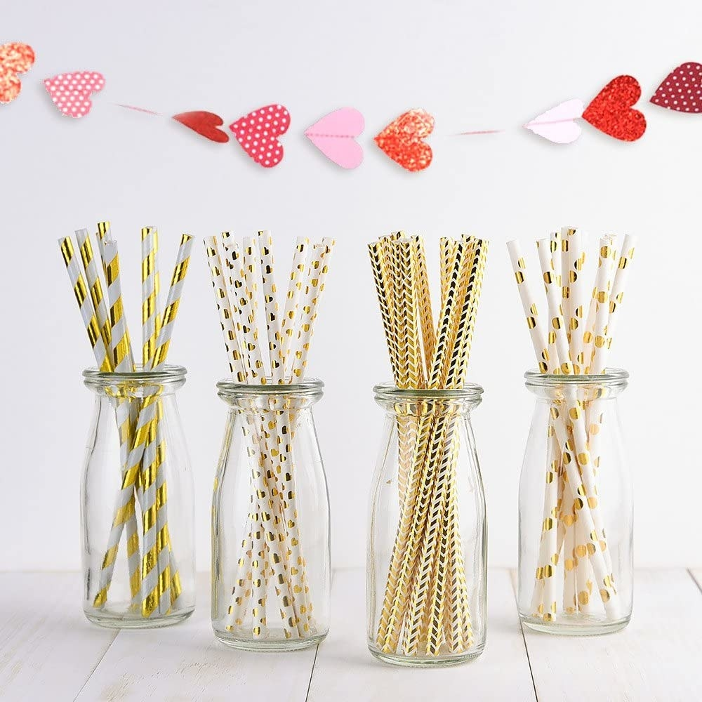 Straws with sparkly gold accents in jars on a table