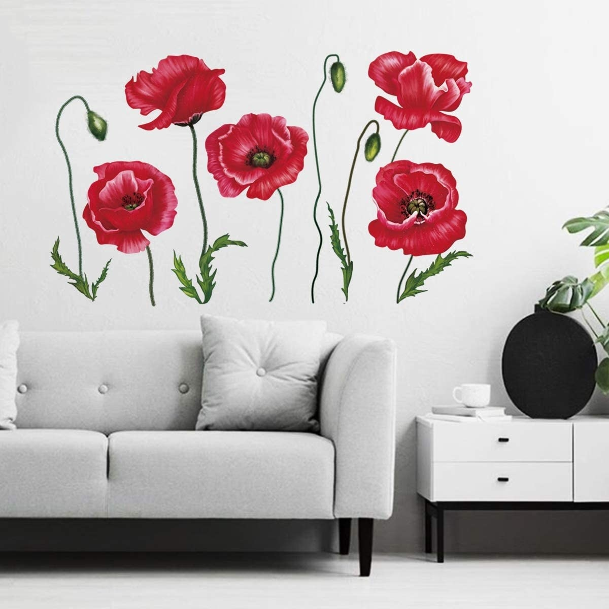 Wall decals of poppies on a wall in a room with a couch and a coffee table