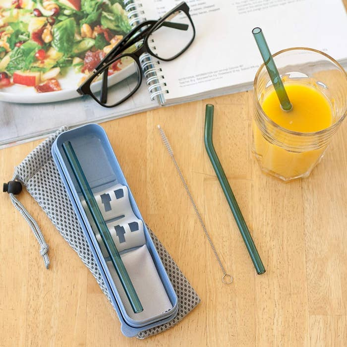 One straw in a drink, one straw and the cleaning brush on a table, and one straw in the case
