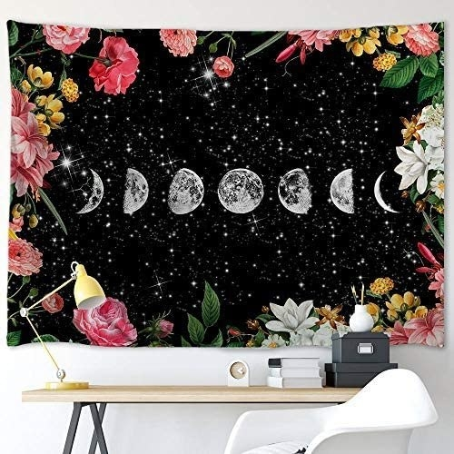 A tapestry with the phases of the moon and flowers is hung on a wall
