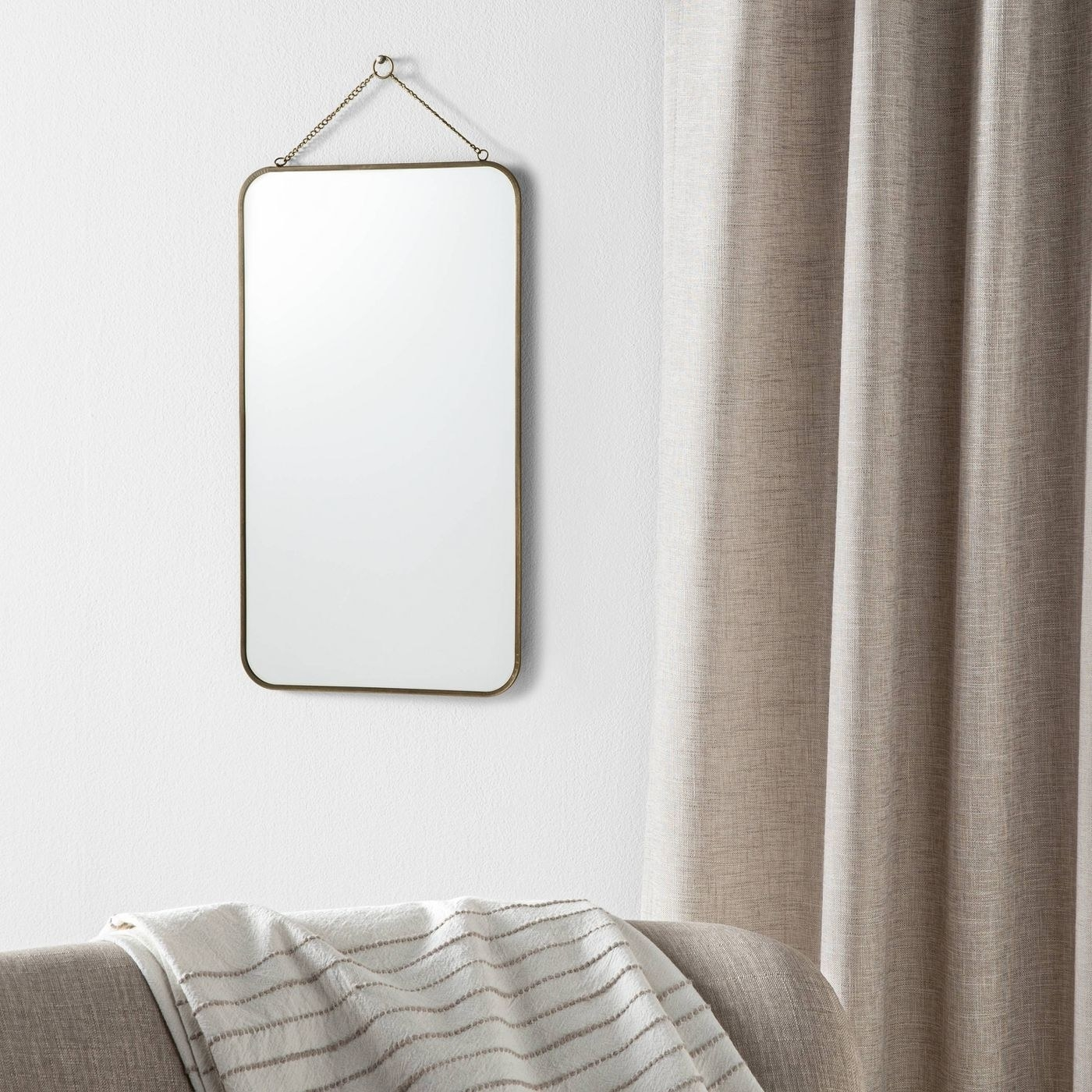 The rectangular mirror with brass-finish metal frame