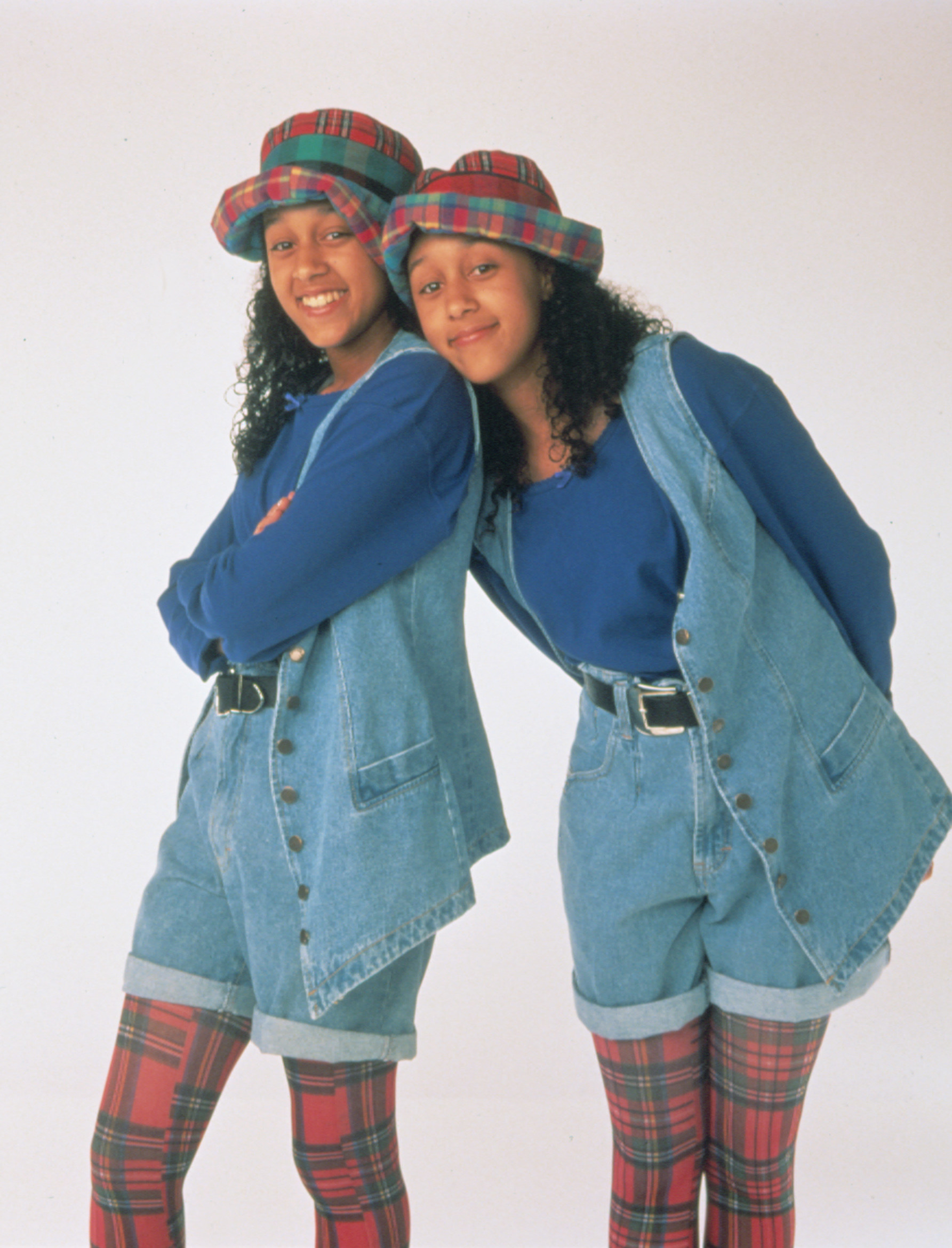 """Tia and Tamera Mowry wearing denim jumpsuits and hats as their """"Sister, Sister"""" characters"""
