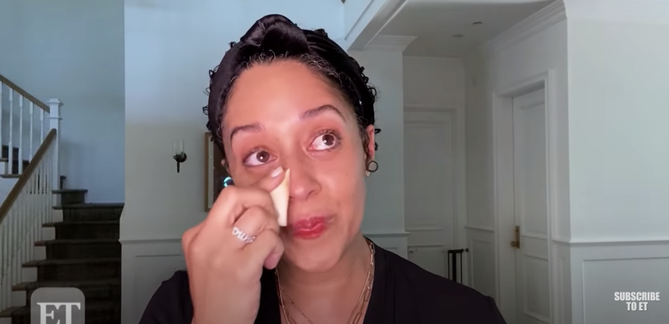 Tia wipes away her tears with a makeup sponge