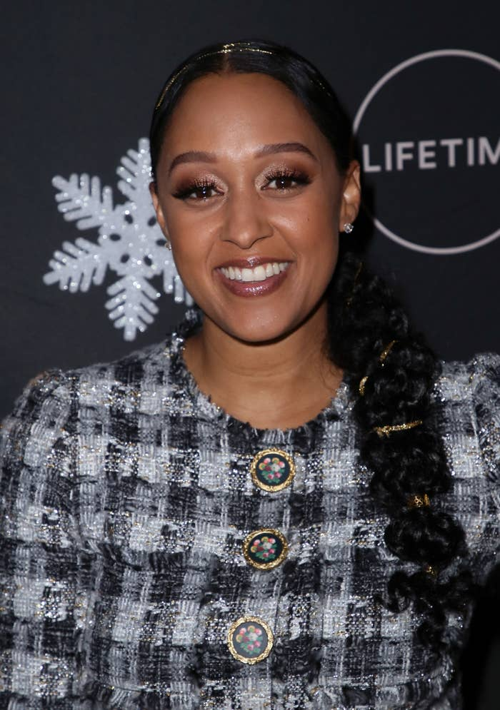 Tia Mowry smiles at an event wearing a long braided ponytail
