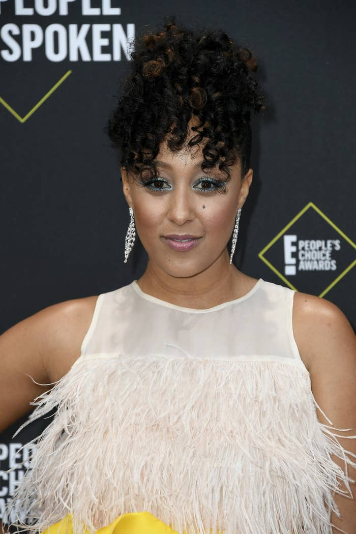 Tamera Mowry smiles at an event wearing a curly up-do hairstyle