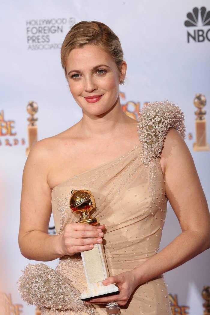 Drew Barrymore holding a Golden Globe award