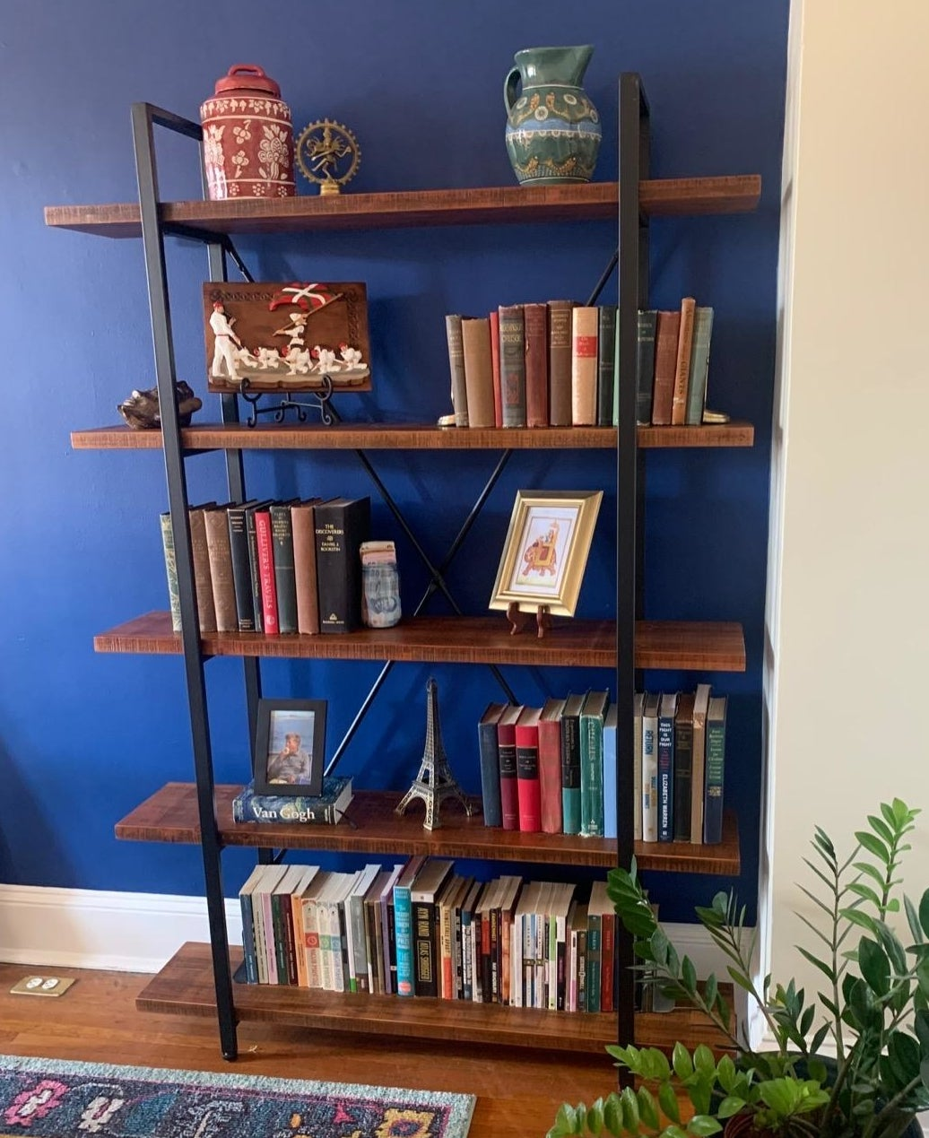 Reviewer pic of the five-shelf bookcase with books, pictures, and other trinkets on each shelf.