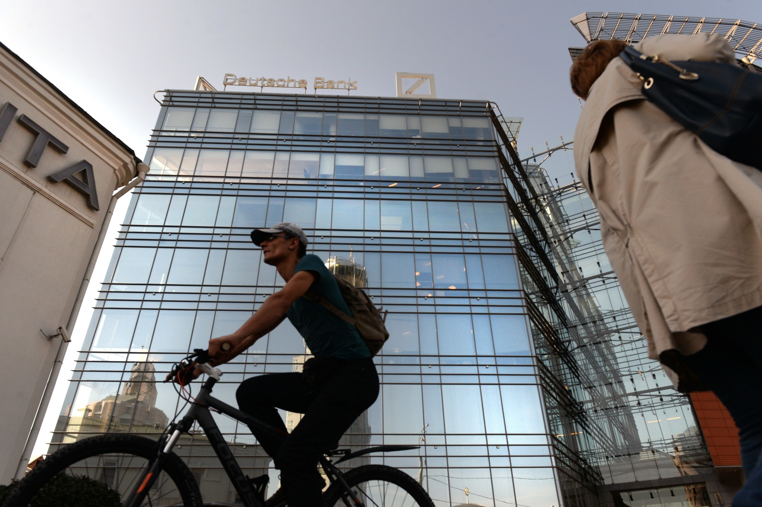 A cyclist rides in front of a towering Deutsche Bank building behind them