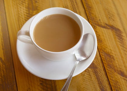 a cup of chai with a saucer and spoon