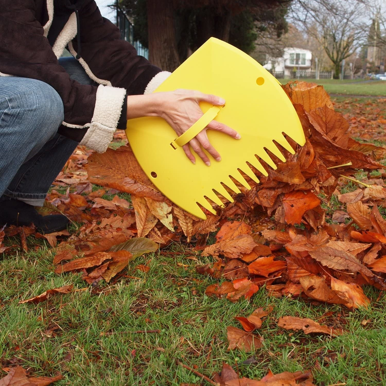 A person picking up a pile of leaves with huge claw-like leaf scoops on their hands