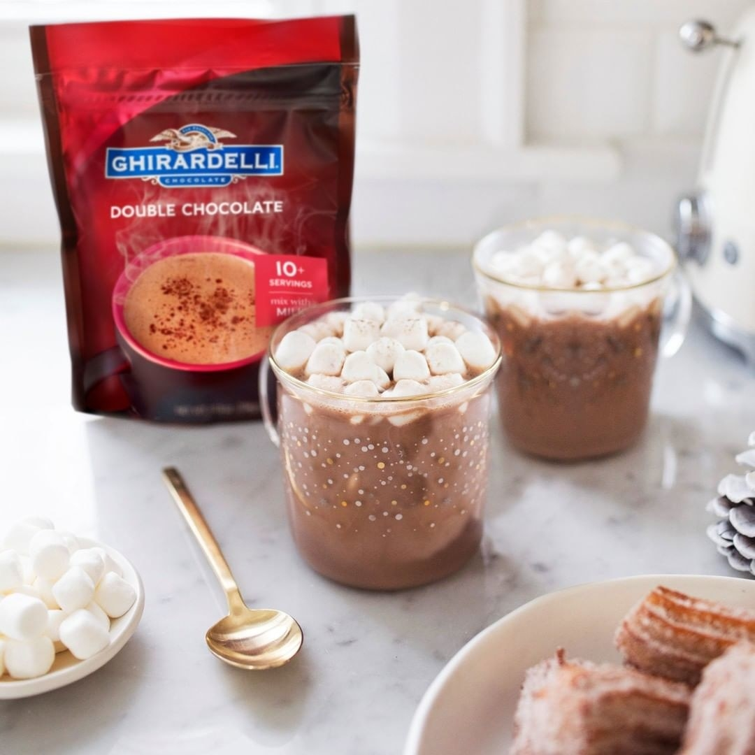 Two glass cups of hot chocolate with marshmallows on top and a small package of hot chocolate mix beside them