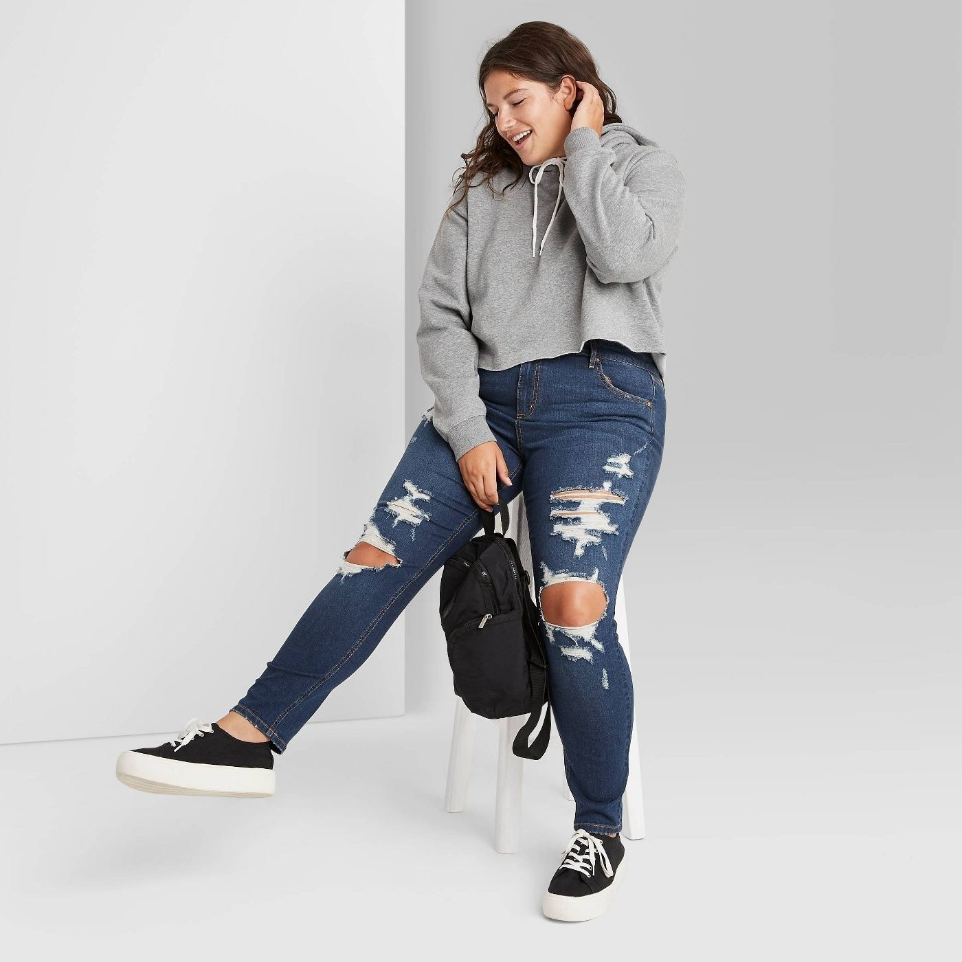 Model wearing the distressed blue jeans