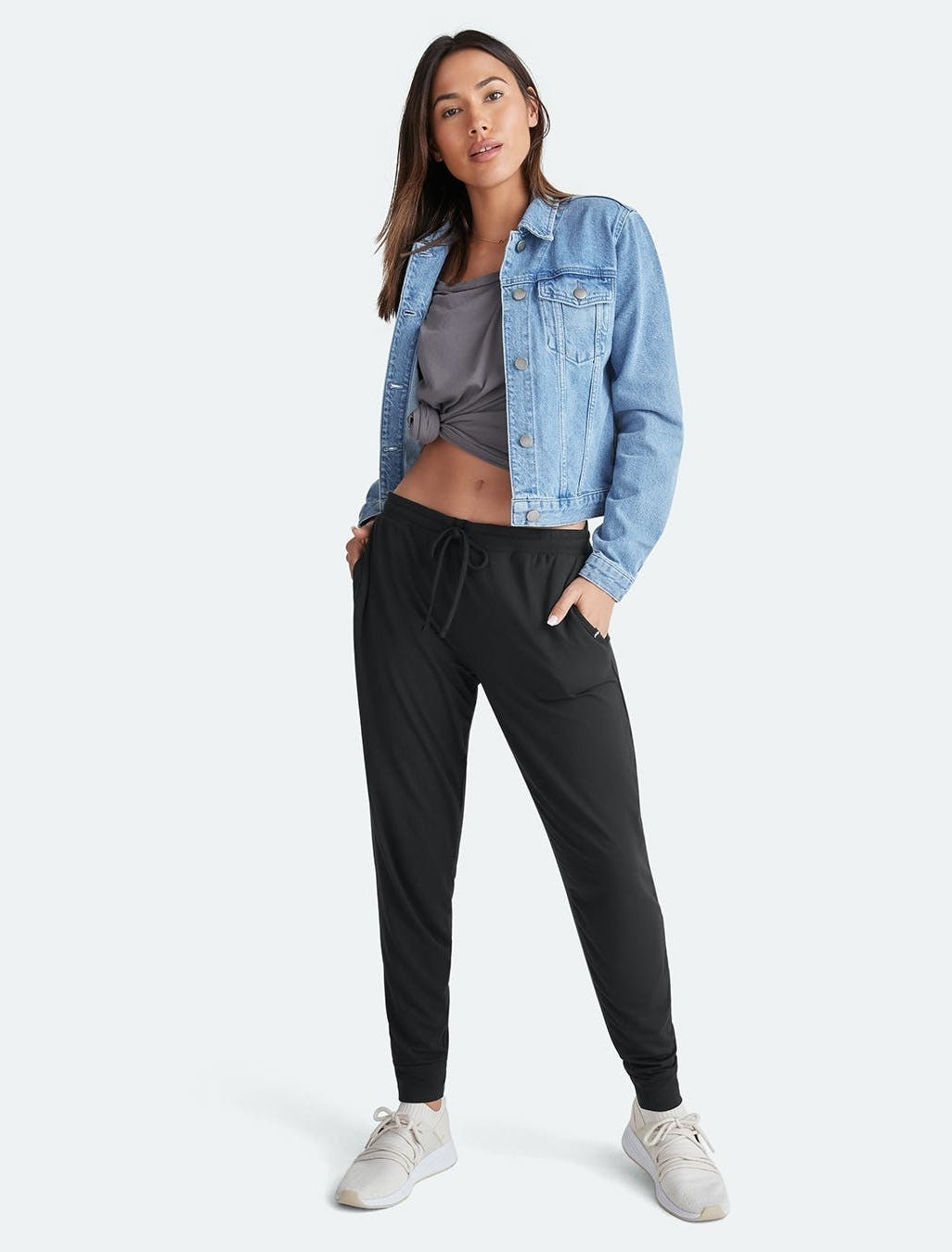 a model wearing black jogger pants with a denim jacket and sneakers