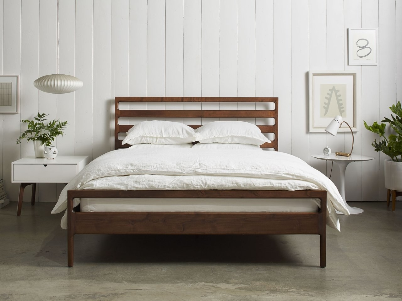 Wood bed frame with slots in the headboard in a bedroom.