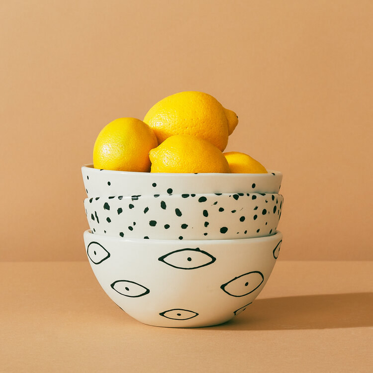 Stack of white ceramic bowls with minimalist eyes, speckles, and dots painted in black