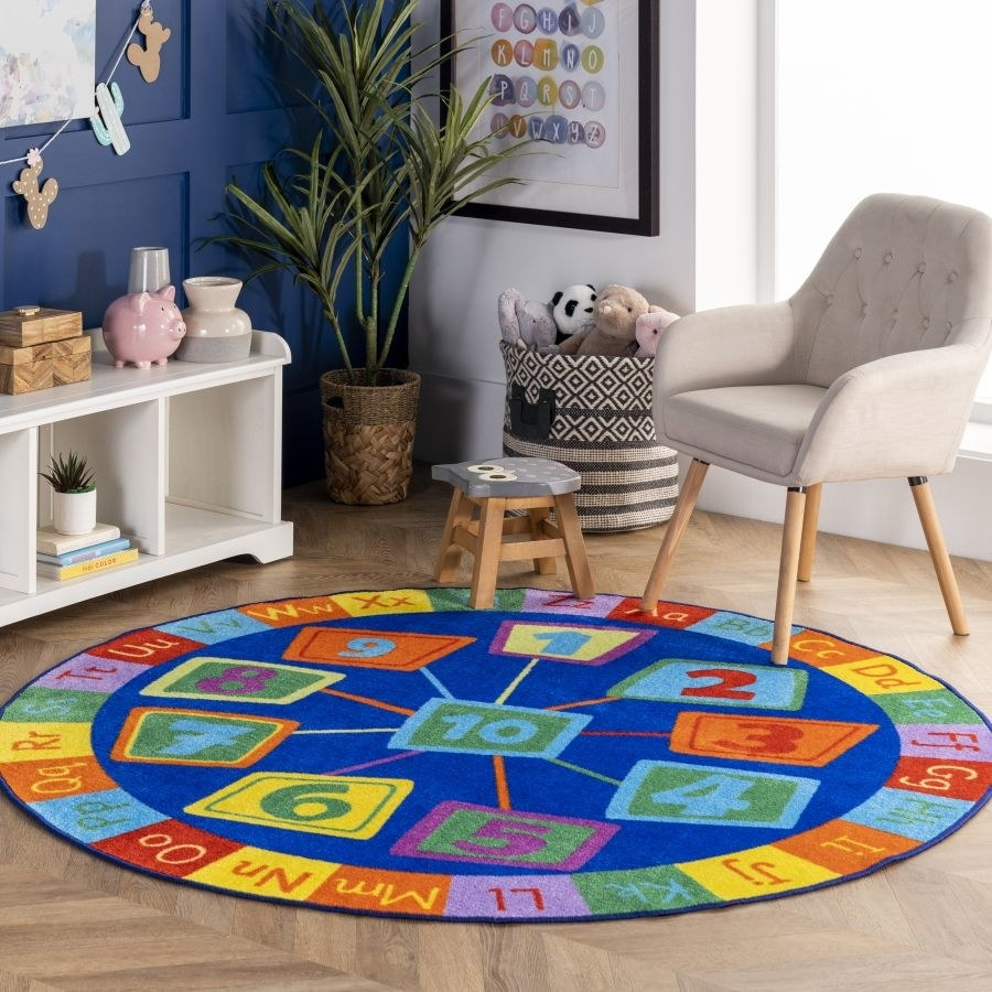 A circular blue rug with a colorful alphabet around the edge and numbers in the center