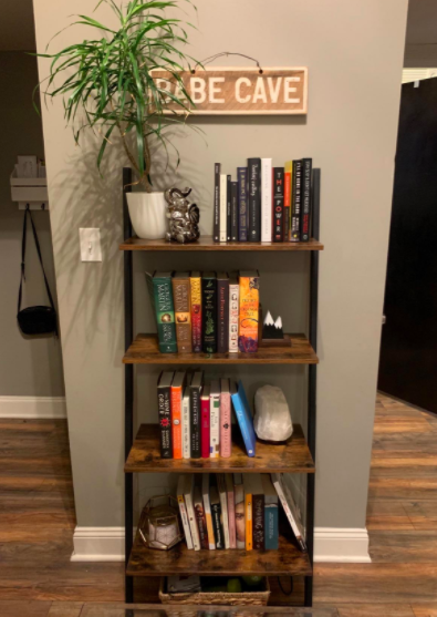 Reviewer props wooden ladder shelf filled with books and trinkets against an unused hallway wall