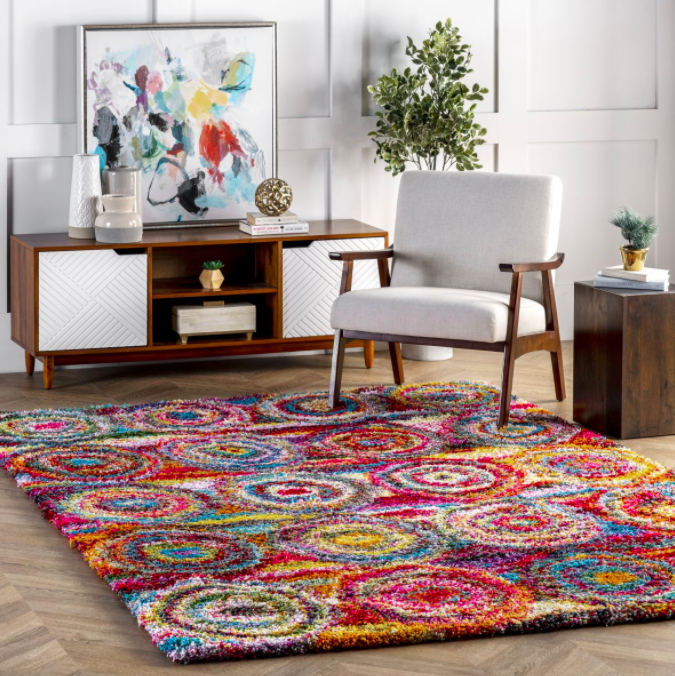 Square-shaped rug with abstract colorful circles on a hardwood floor next to white armchair and wooden TV stand