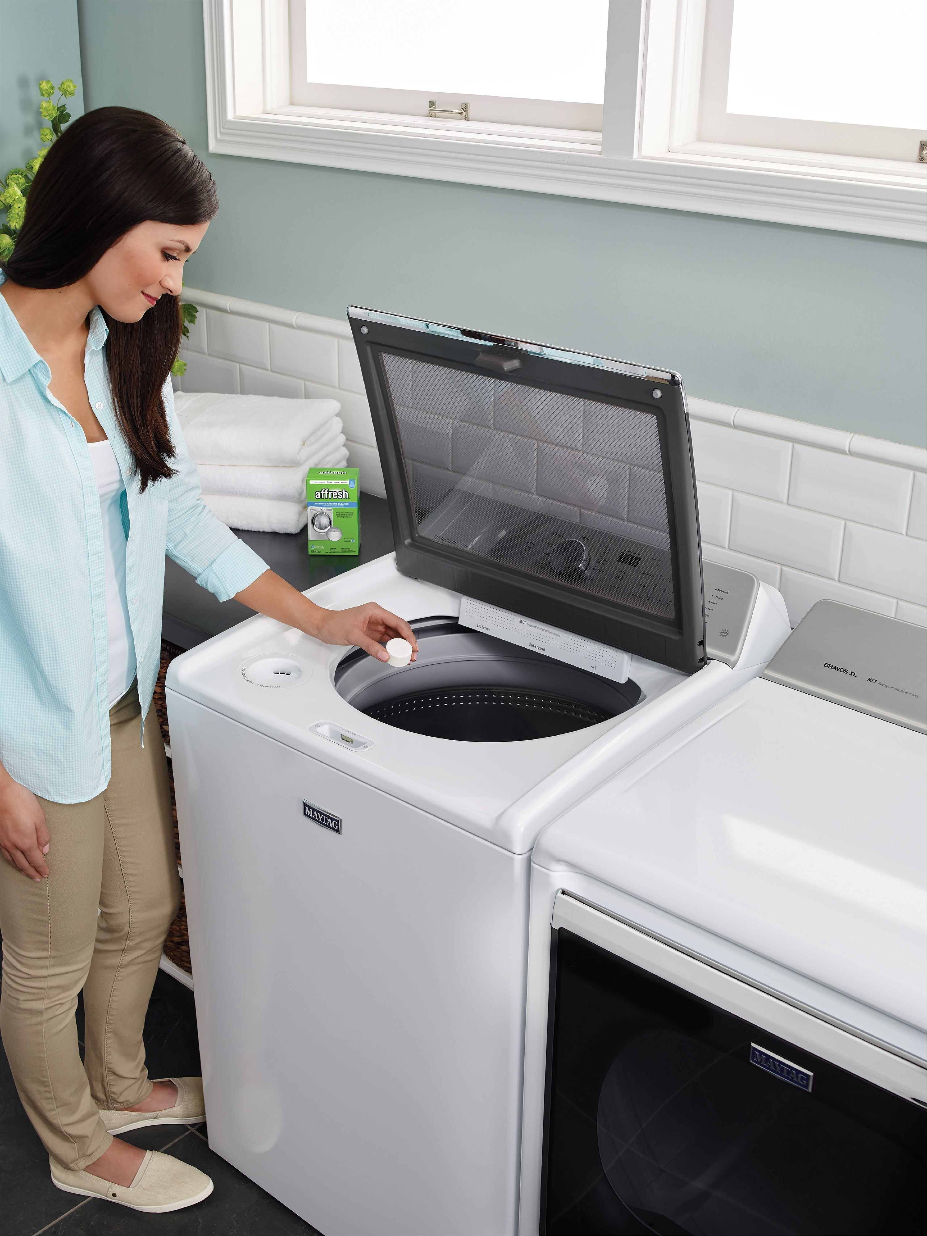 A model placing an Affresh tablet in the washing machine