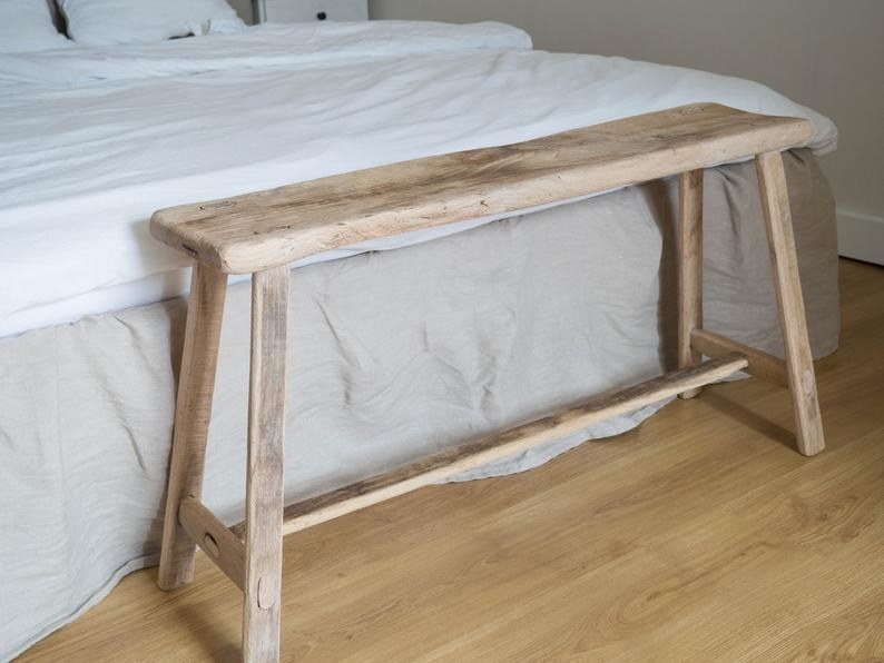 The wood bench with wood legs and a beam across the bottom middle in front of a bed.