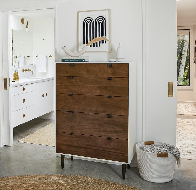 The wood five-drawer dresser with leather pull tabs and white frame with dark brown legs in a room.
