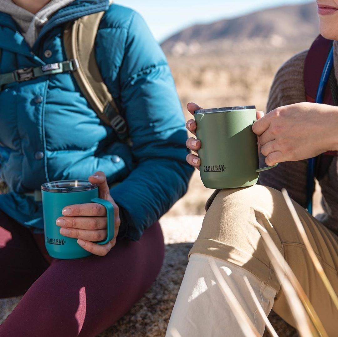 a couple each holding a camelbak mug with a handle