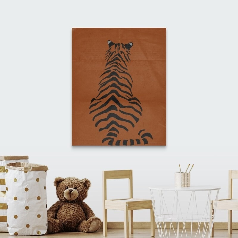 A wall hanging of the back of a tiger in black stripes on an orange canvas