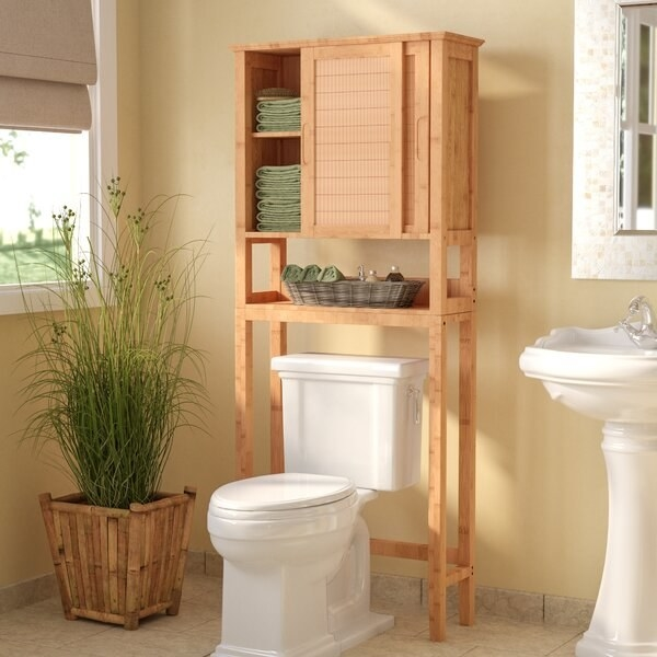The Beachcrest Home Natural Muller Over-the-Toilet Storage in a bathroom