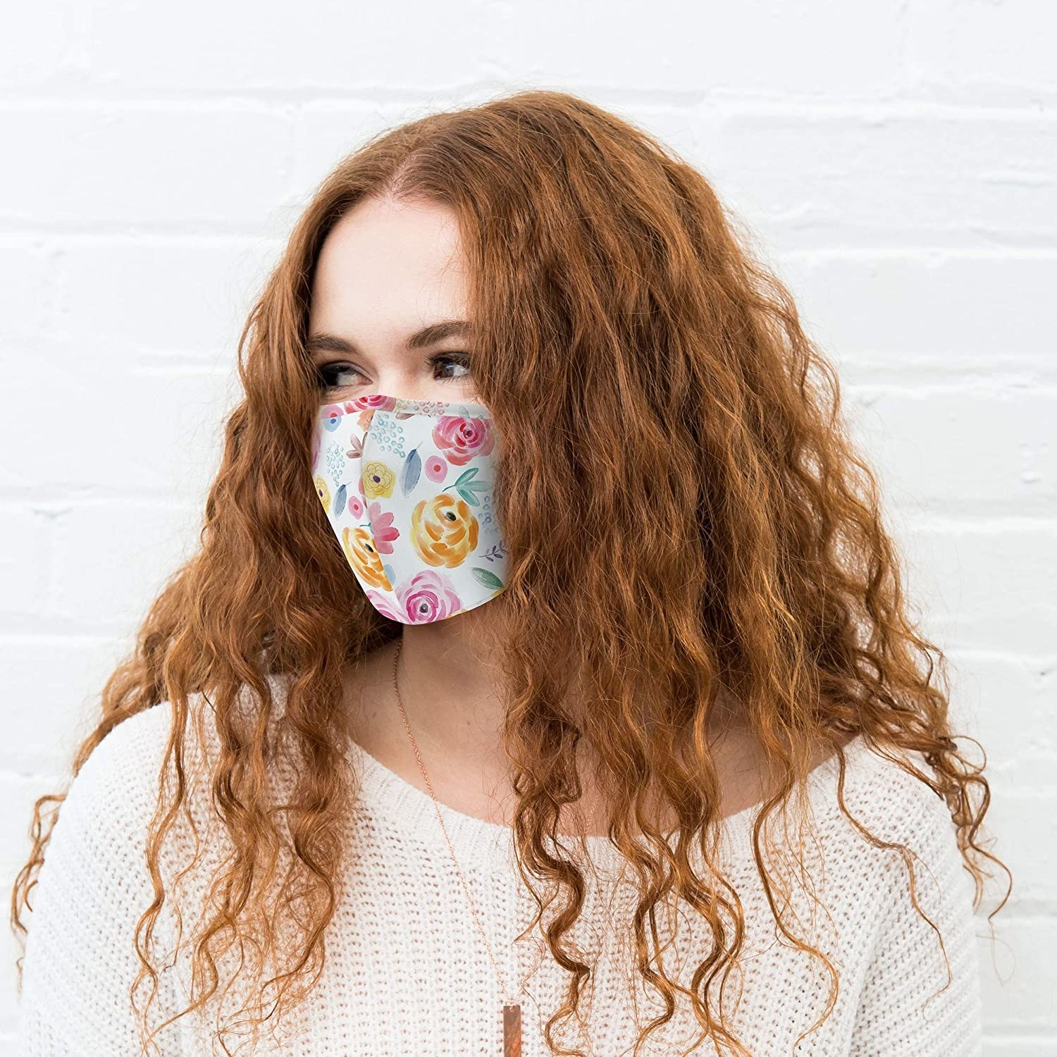 A person wears a floral mask
