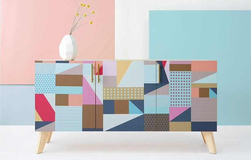 Three-door sideboard with wood legs and a geometric multi-colored pattern on the front.