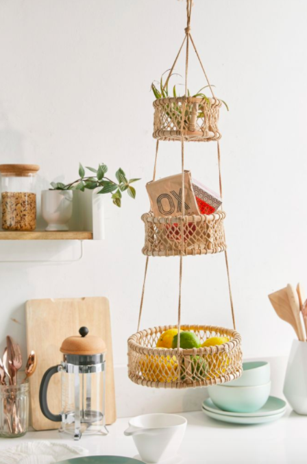 Light brown hanging basket with three compartments for lemons, herbs, and cookbooks in a minimal-inspired kitchen