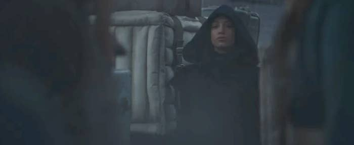 Sasha Banks in The Mandalorian standing around in a black hooded outfit