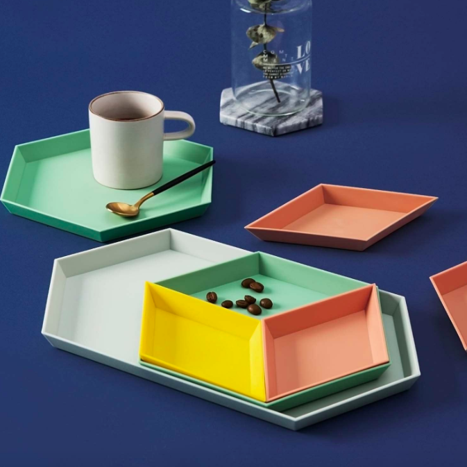 Pink, white, green, and yellow geometric-designed catch trays on a blue table