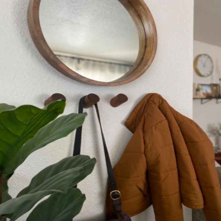 Dark brown wall hooks holding up a black purse and red coat under a mirror