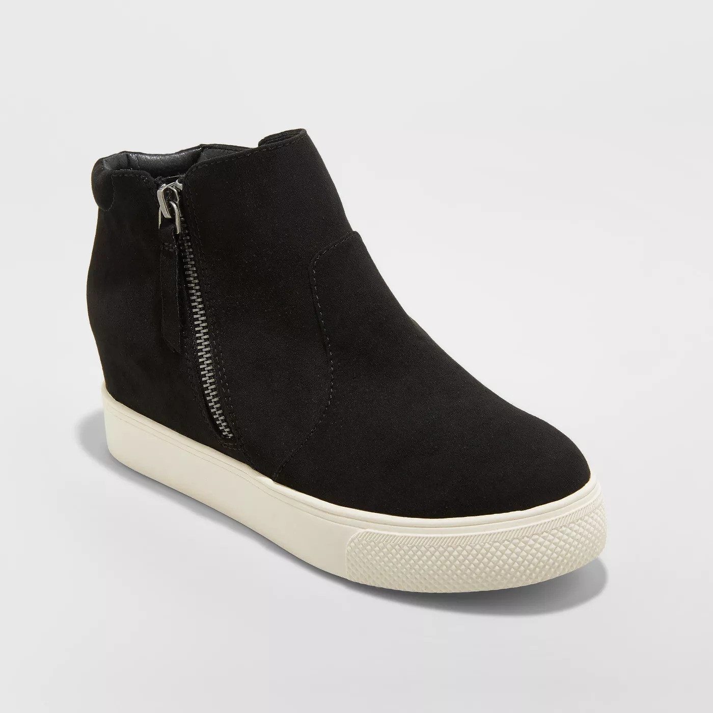A black high top sneaker with a flat rubber sole and zipper on the side