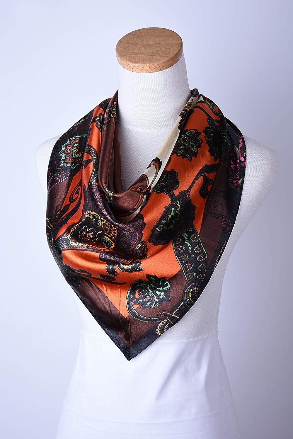 The multicolor (including orange and brown) scarf draped on a mannequin