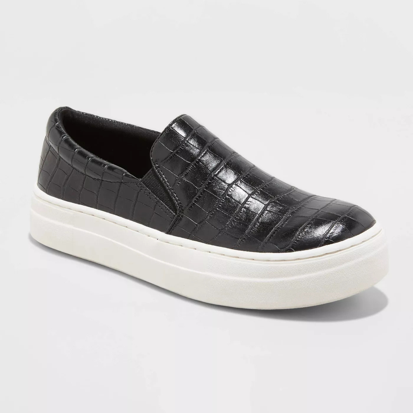 a black faux-snakeskin upper and a white platform rubber sole