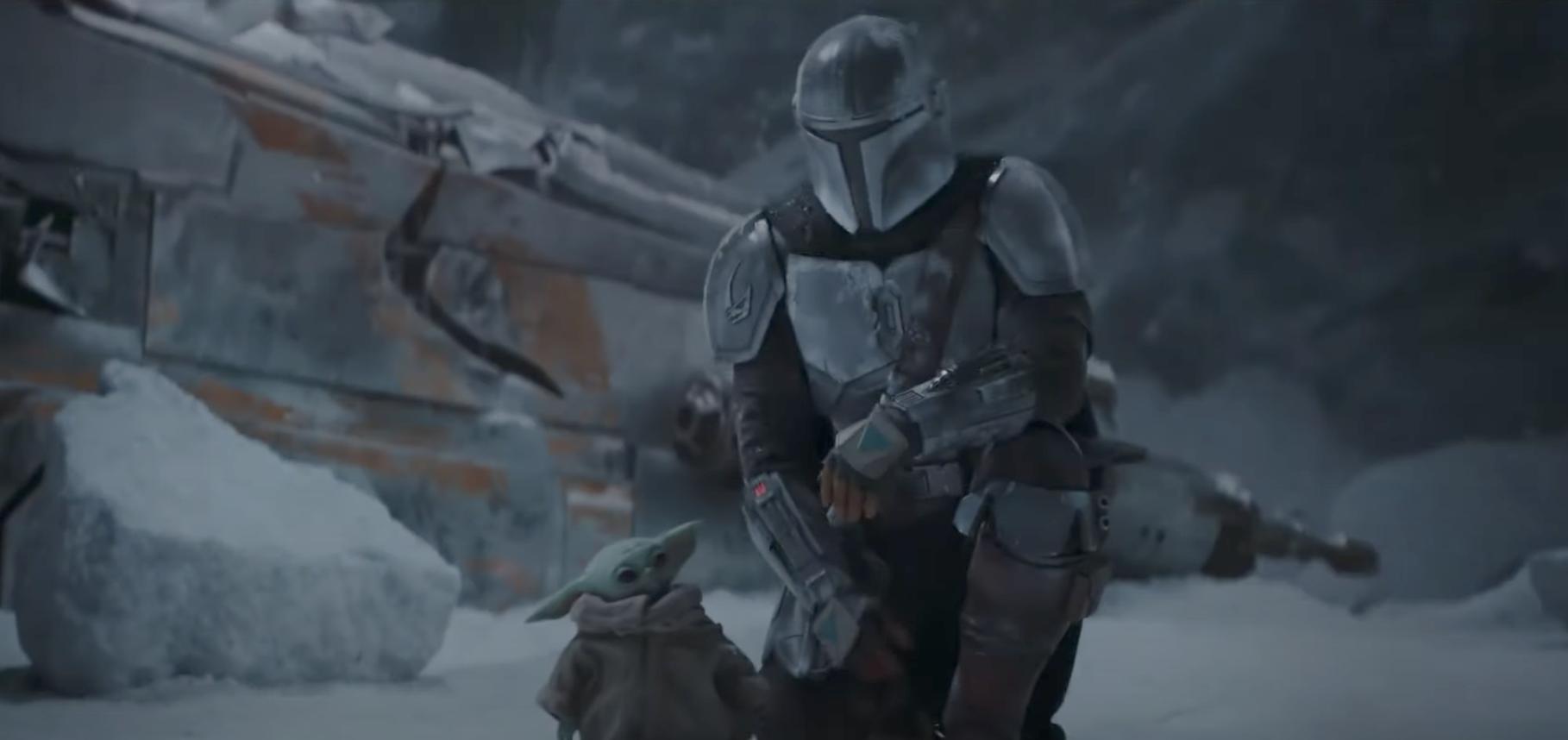 The Mandalorian kneels next to Baby Yoda
