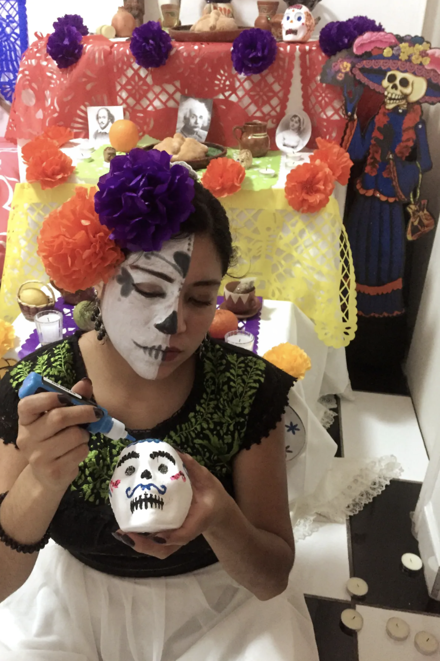 A woman in traditional Mexican Day of the Dead makeup and outfit paints a sugar skull