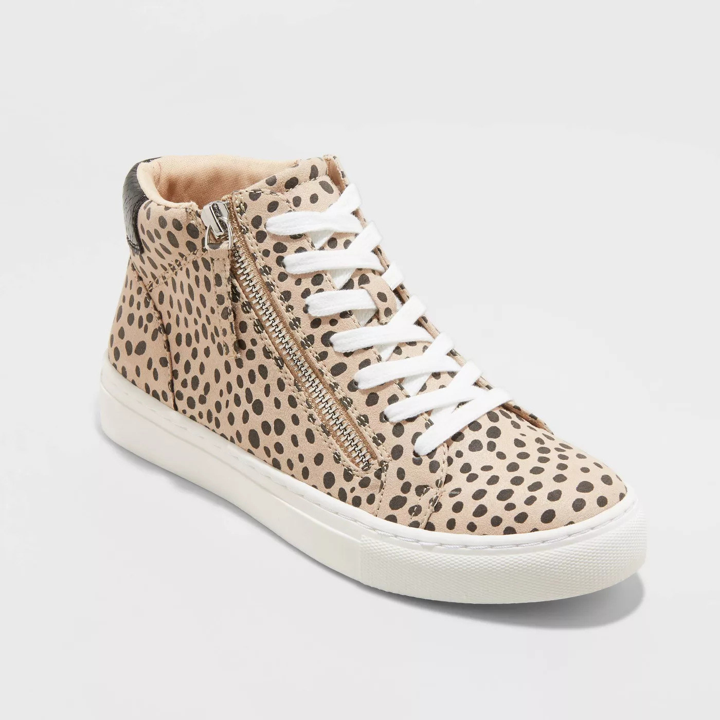 beige high top sneakers with black spots, white laces, and a zipper