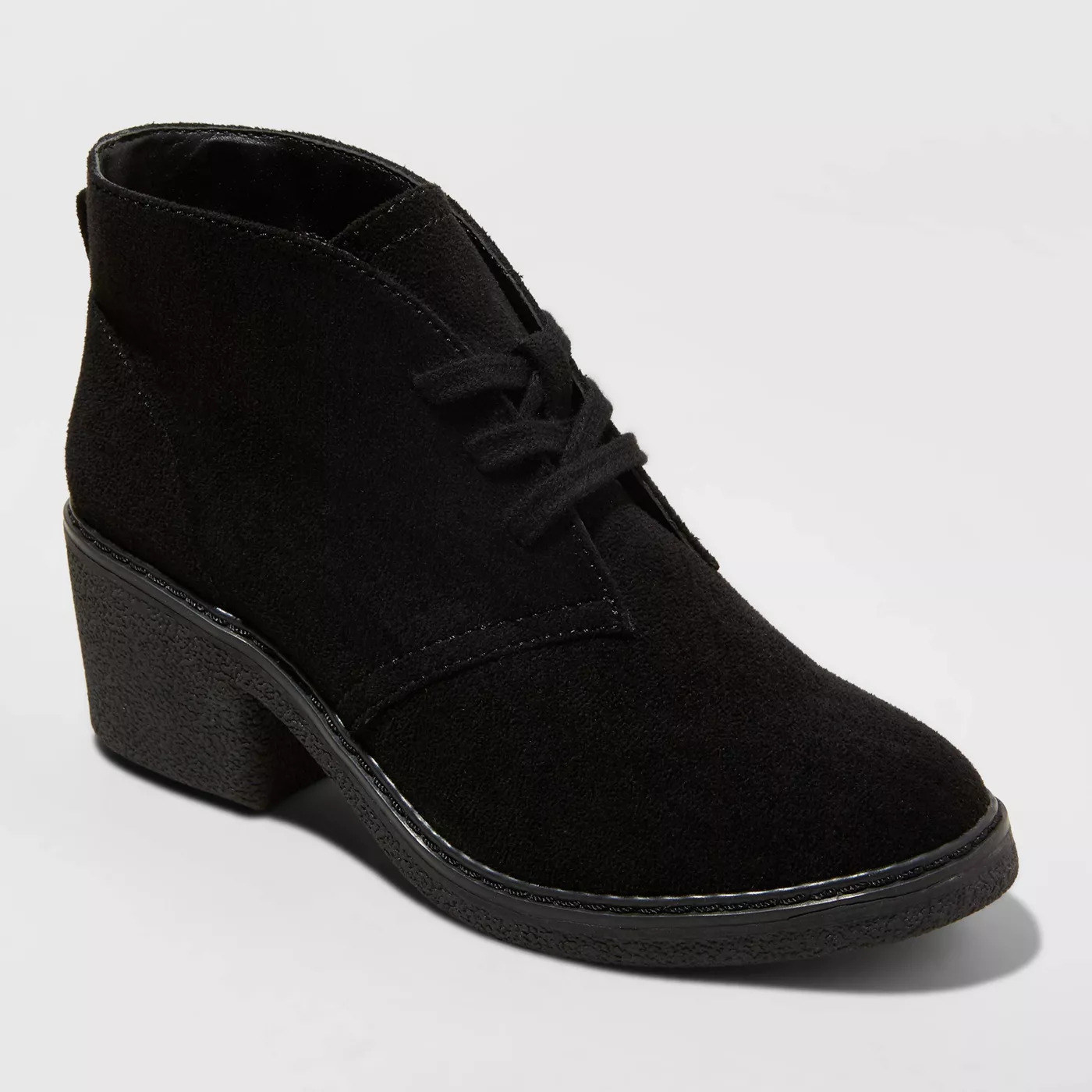 A faux suede black bootie with laces in the front, a low block heel, and a crepe sole