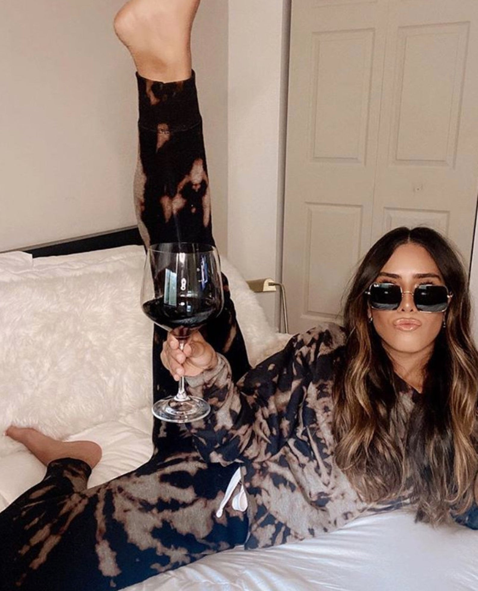 a model wearing the brown tie dye sweatshirt and sweatpants while in bed with a glass of wine