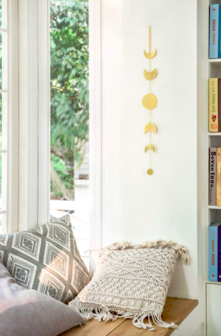 Gold hanging phases of the moon garland on the side of a bright window nook covered. in pillows